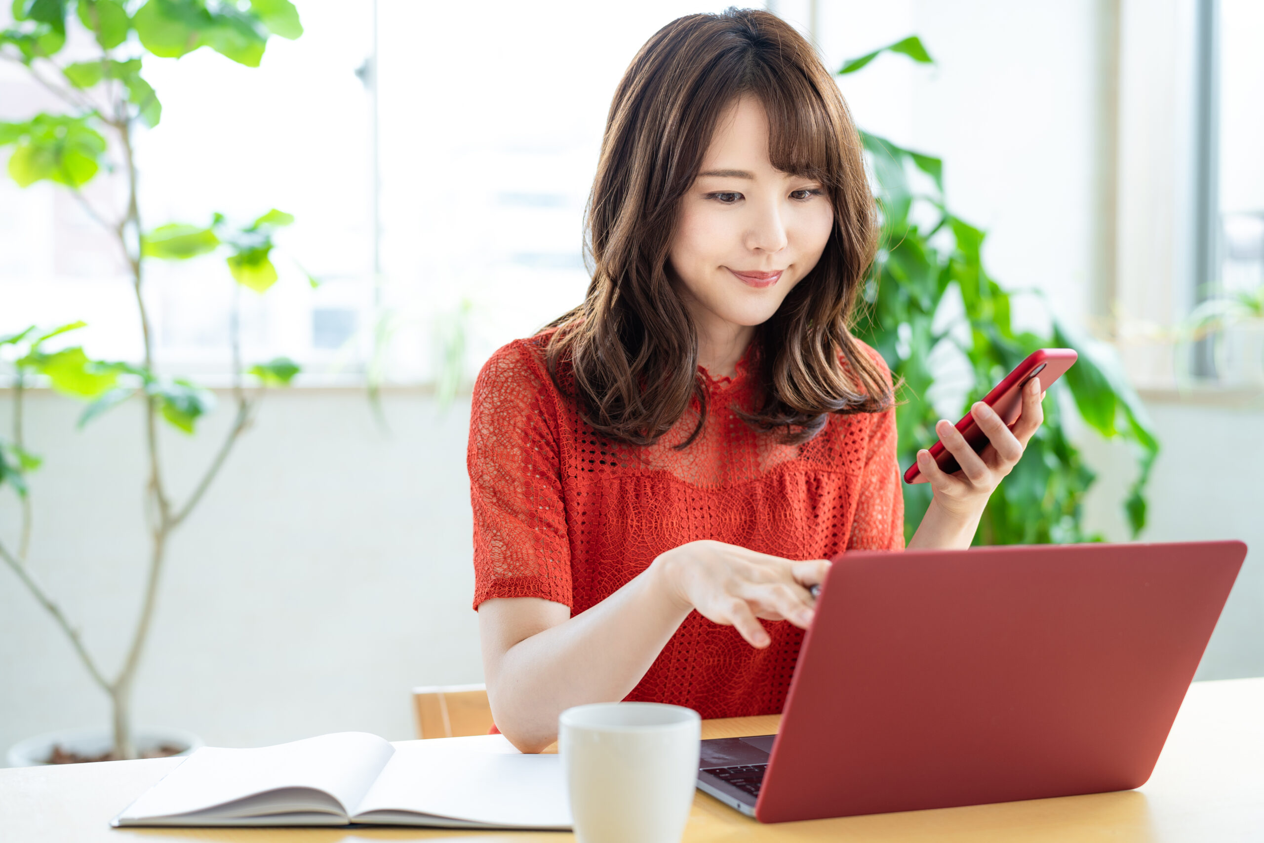 Attractive,Asian,Woman,Using,A,Laptop,Pc,And,A,Smart