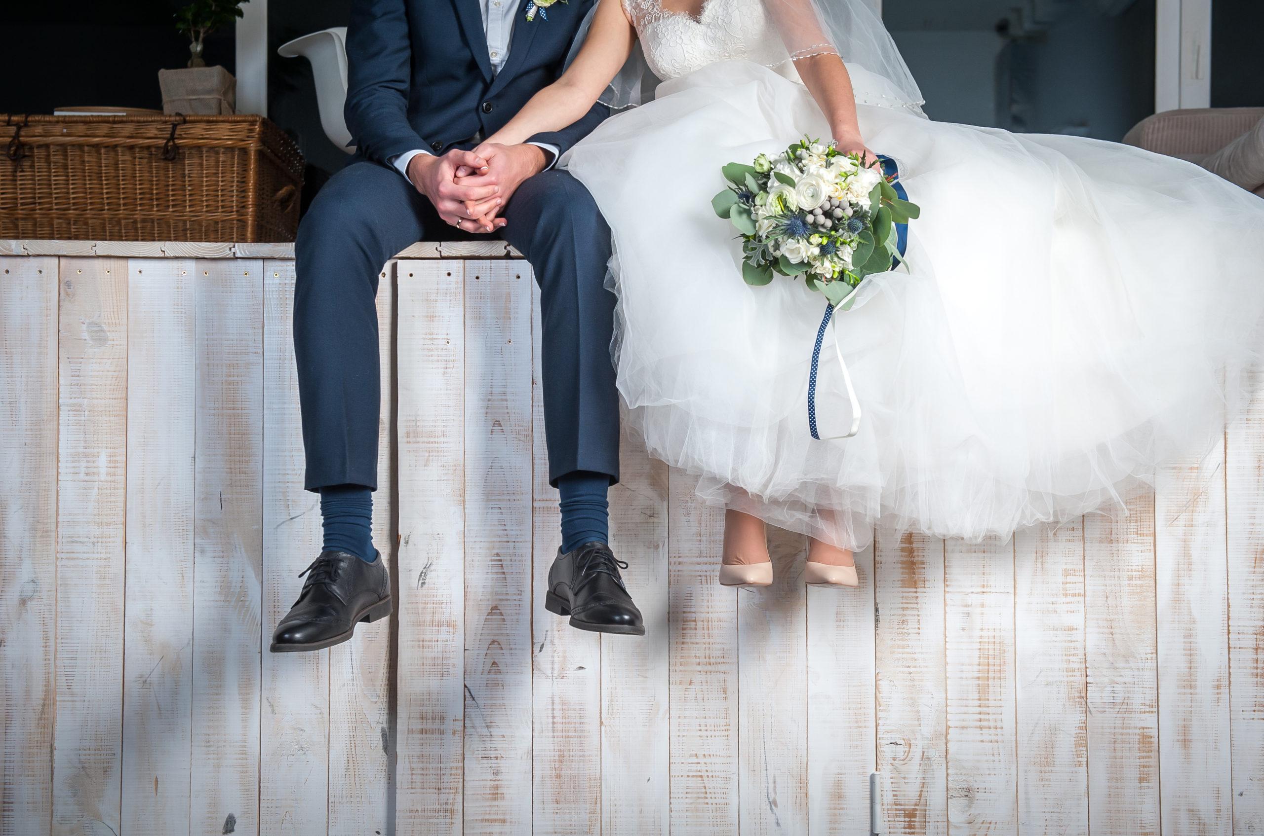 beautiful-wedding-couple-sitting-on-wooden-597022424