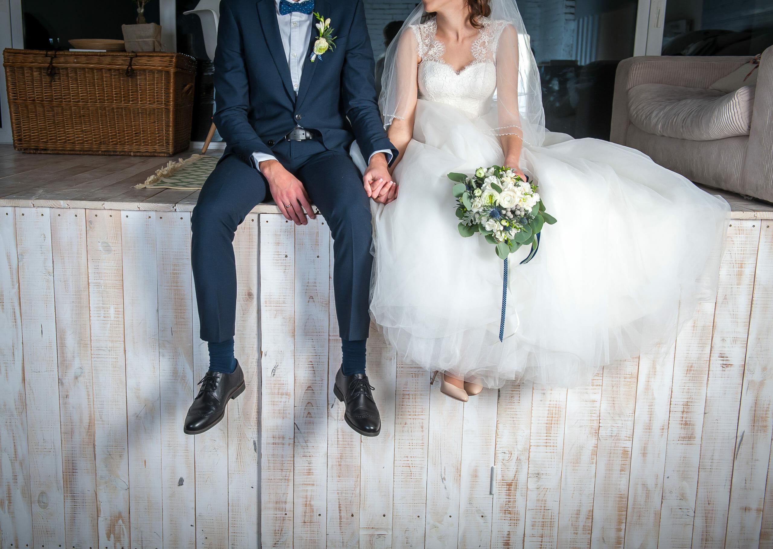 beautiful-wedding-couple-sitting-on-wooden-614783756