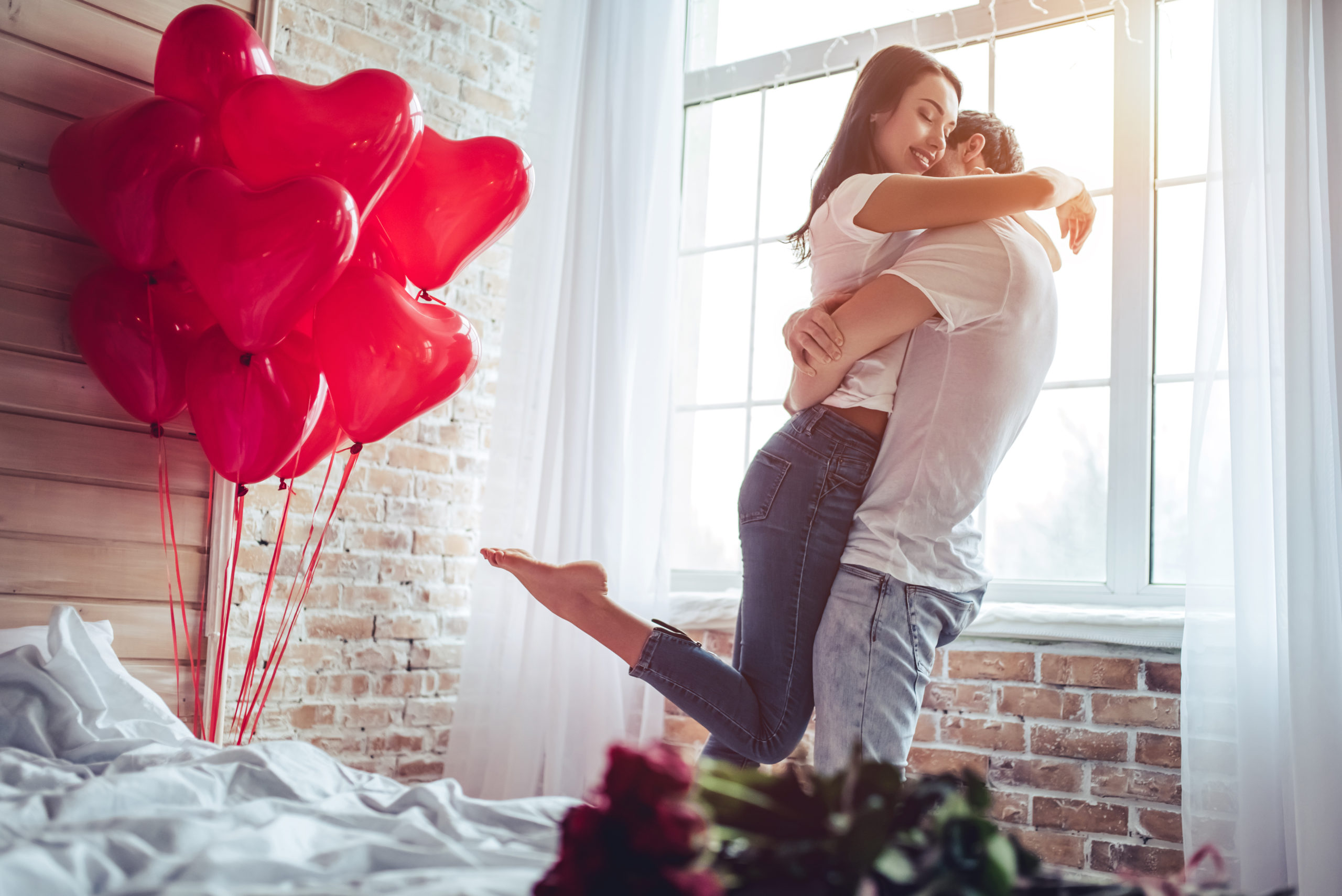 beautiful-young-couple-home-hugging-kissing-789710509