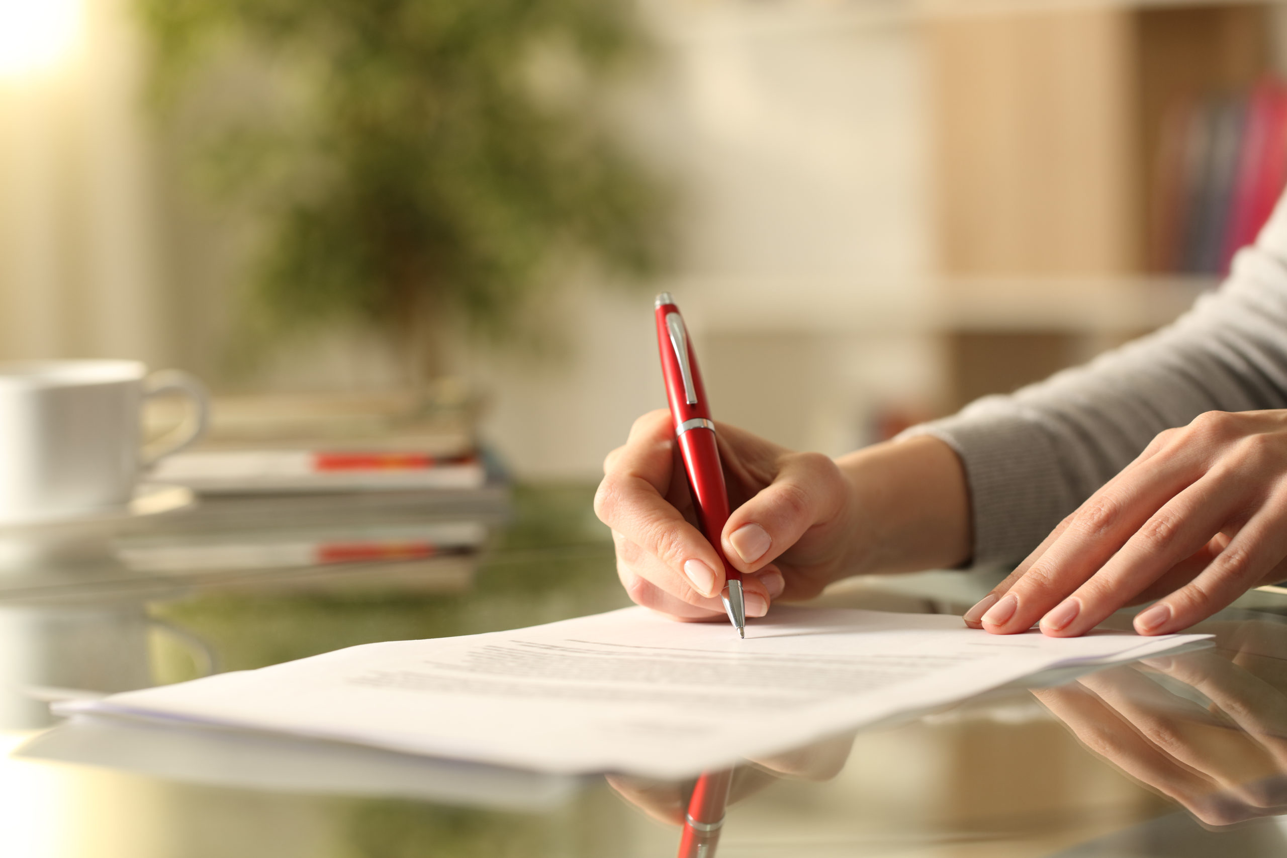 Close,Up,Of,Woman,Hands,Signing,Document,With,Pen,On