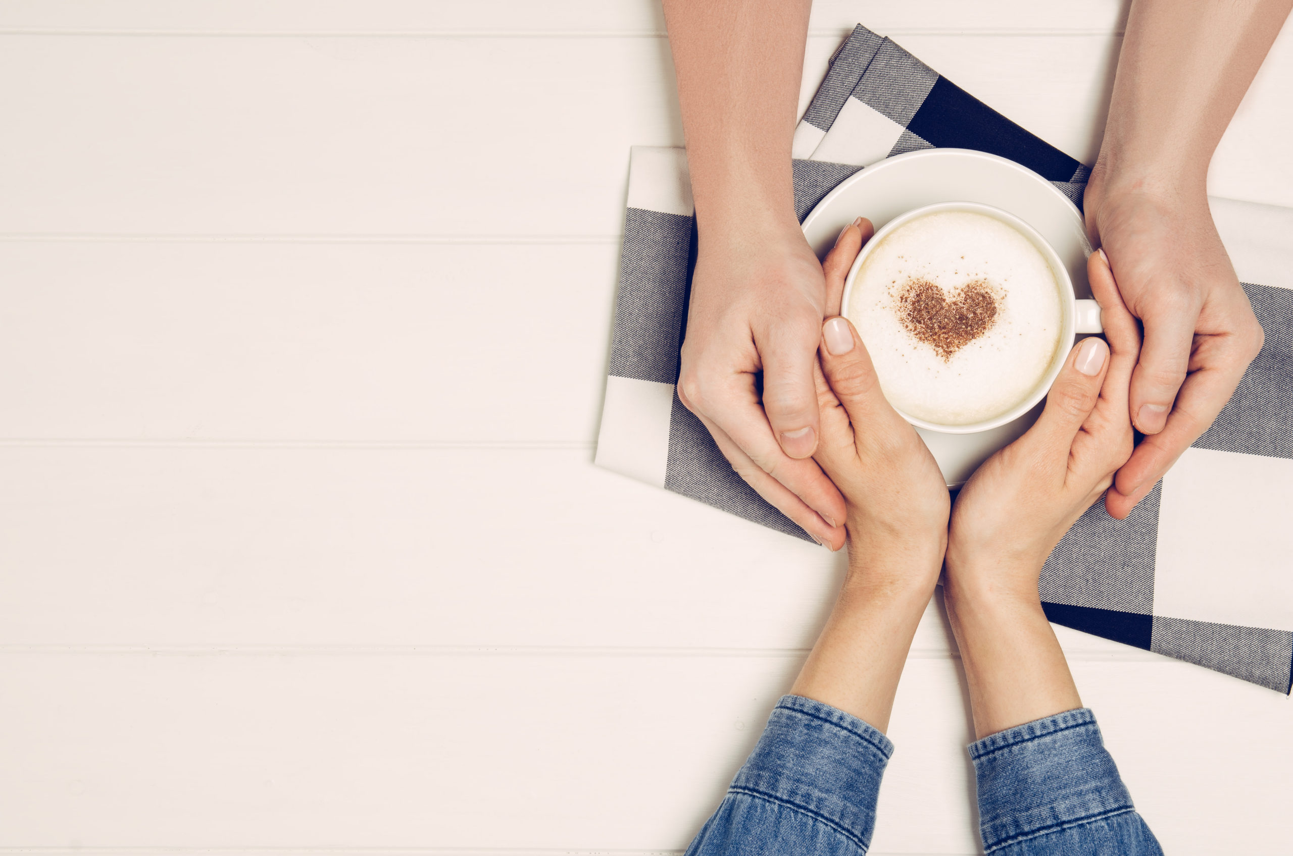 Couple,In,Love,Holding,Hands,With,Coffee,On,White,Wooden
