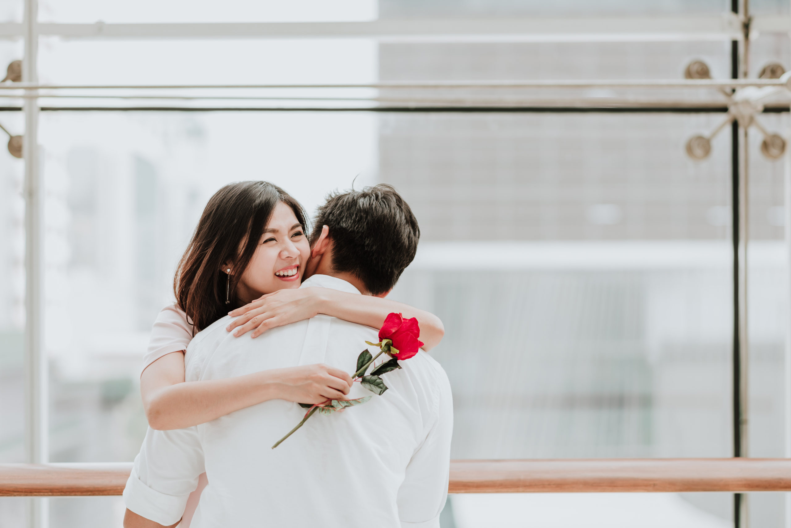 Happy,Beautiful,Young,Asian,Woman,Embracing,Her,Boyfriend,After,Receive
