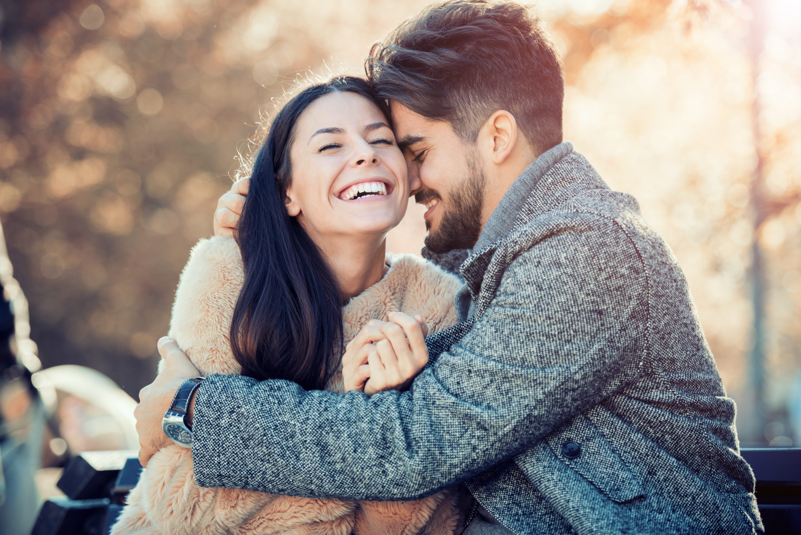 Happy,Young,Couple,Hugging,And,Laughing,Outdoors.