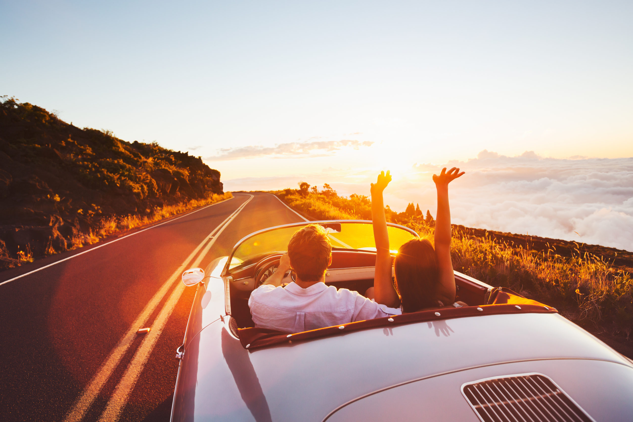 Happy,Couple,Driving,On,Country,Road,Into,The,Sunset,In