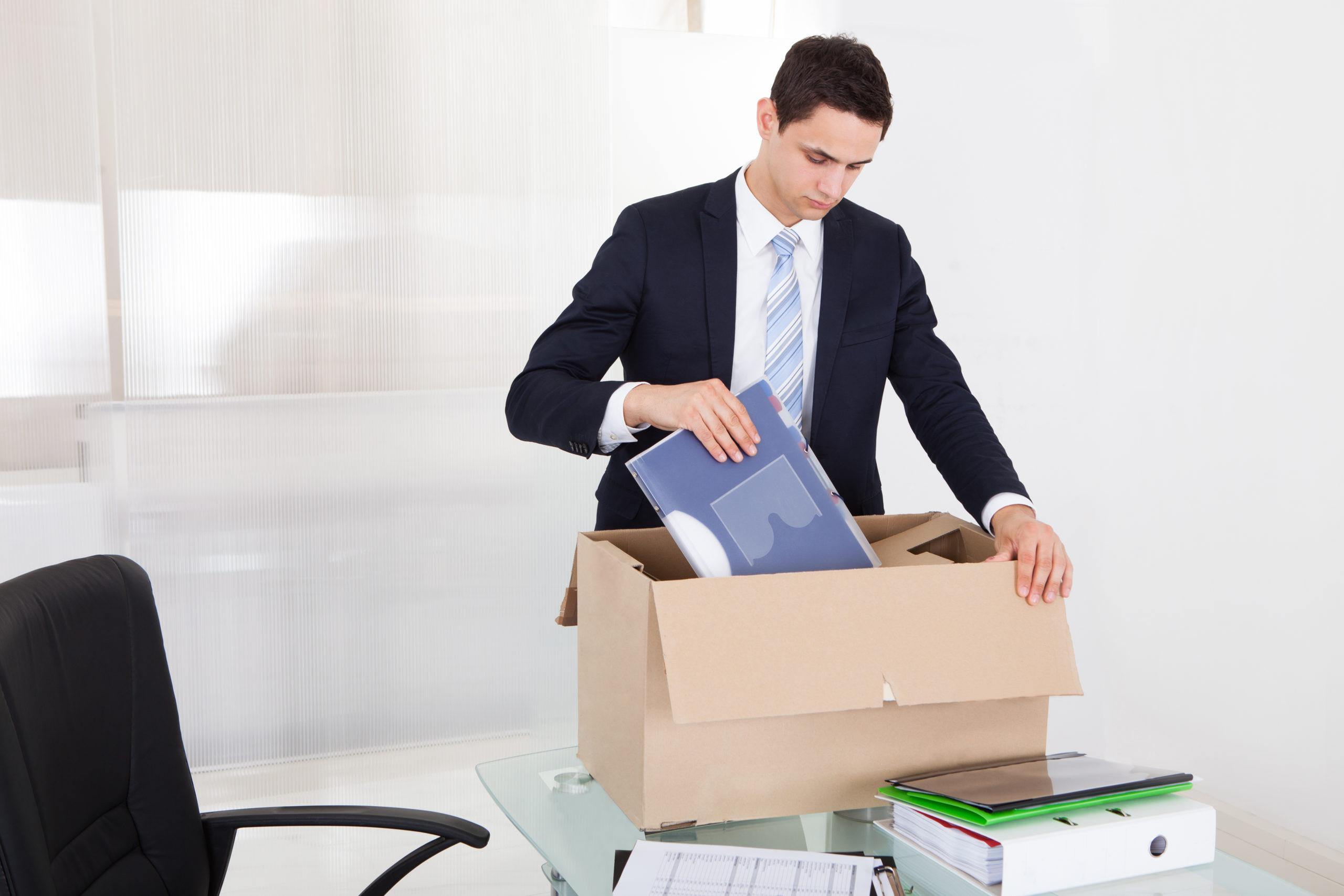 sad-young-businessman-packing-files-cardboard-192002354
