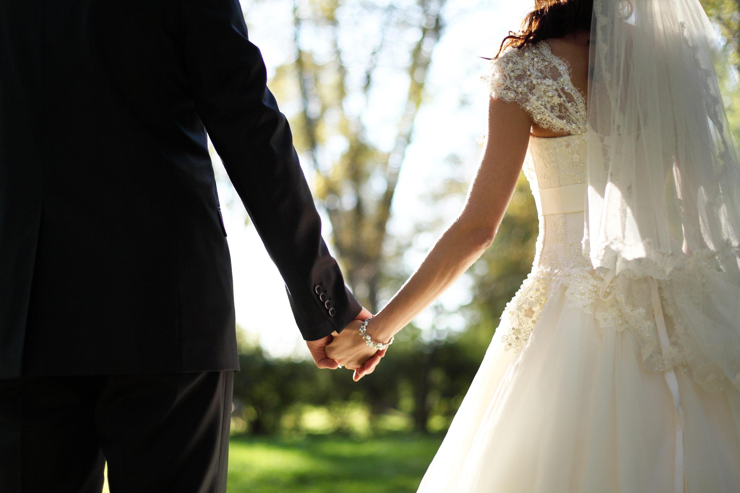 wedding-theme-holding-hands-newlyweds-133378736