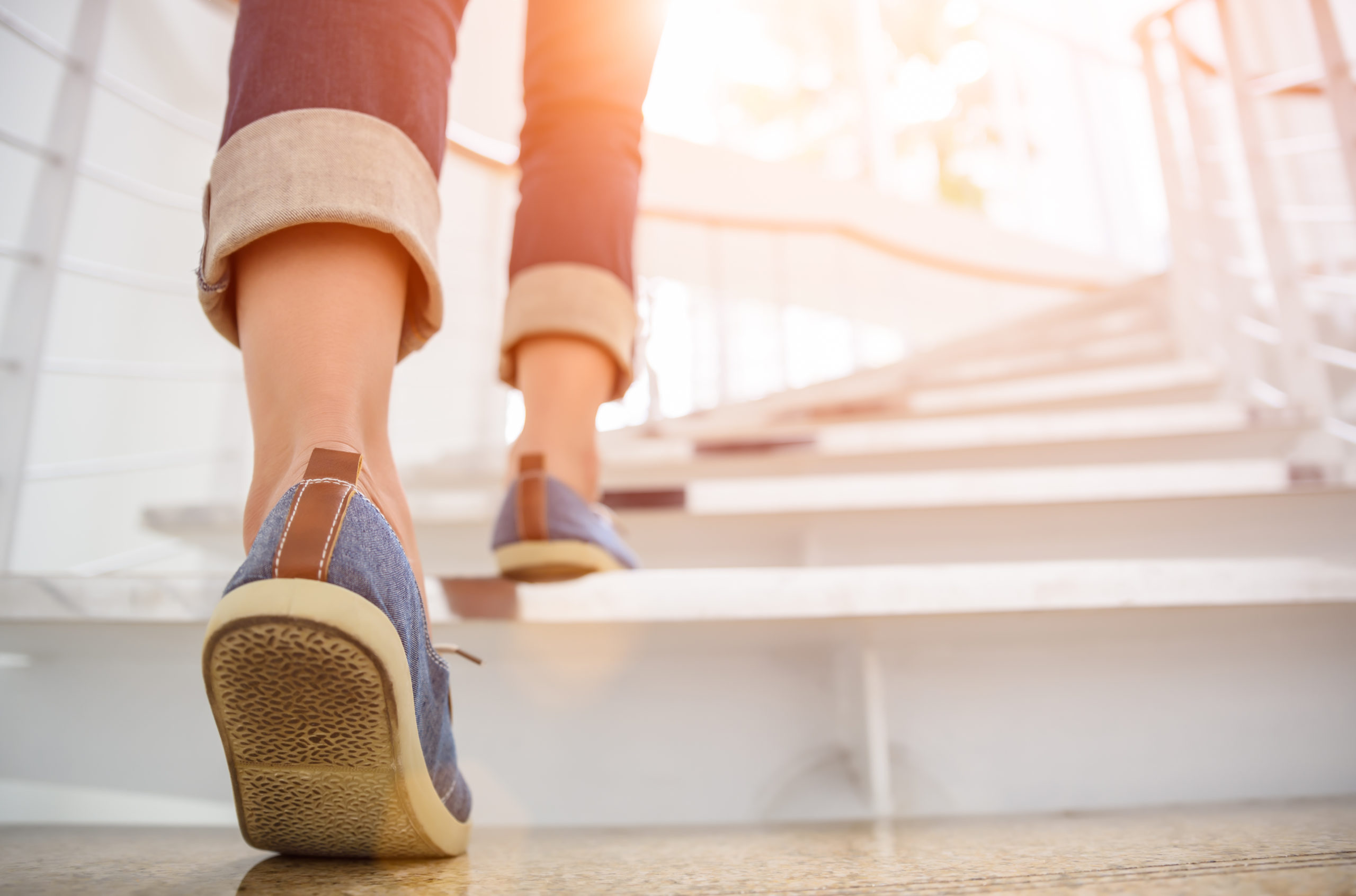 young-adult-woman-walking-stairs-sun-753613000