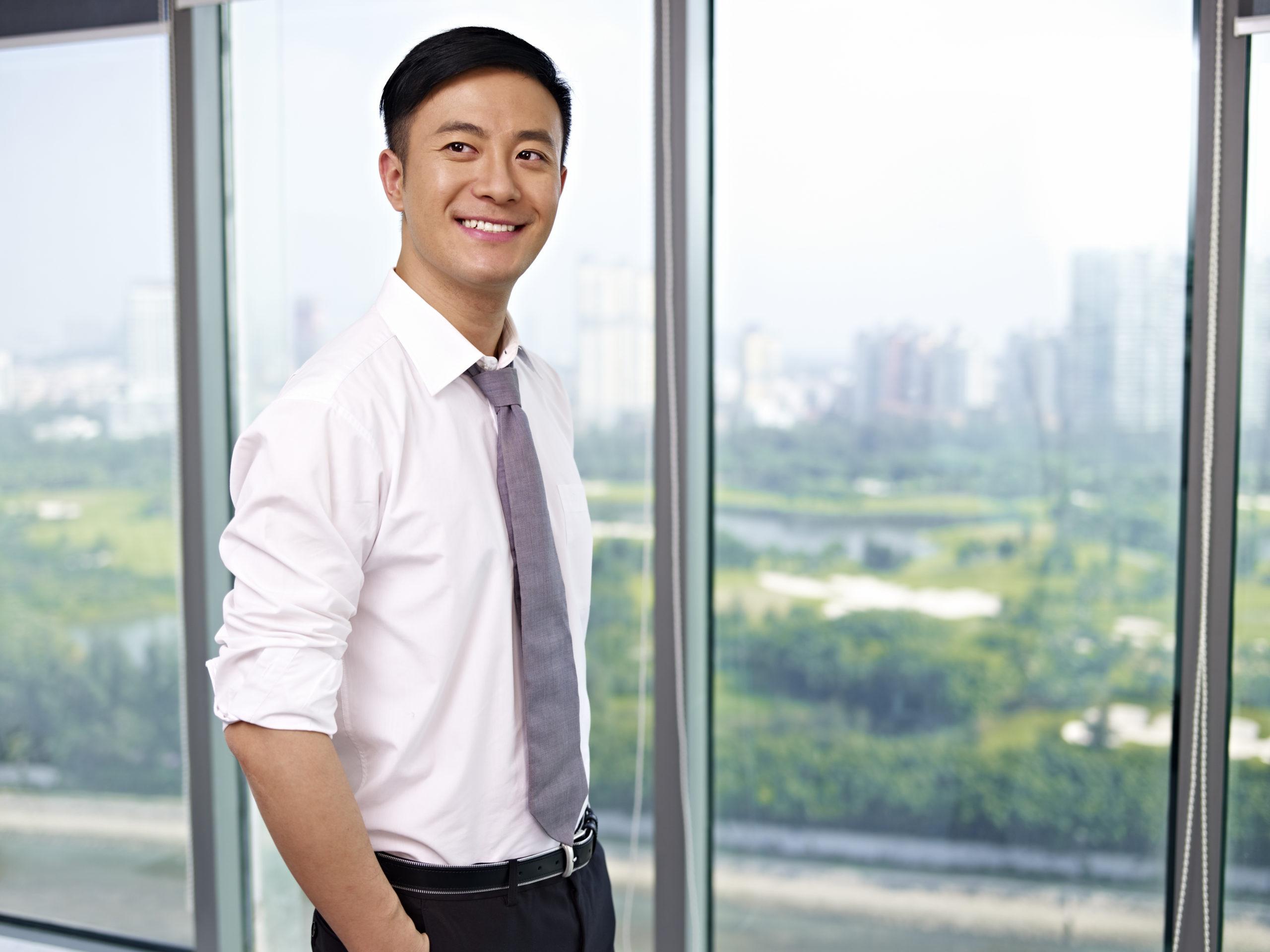 young-asian-business-executive-standing-by-138585860