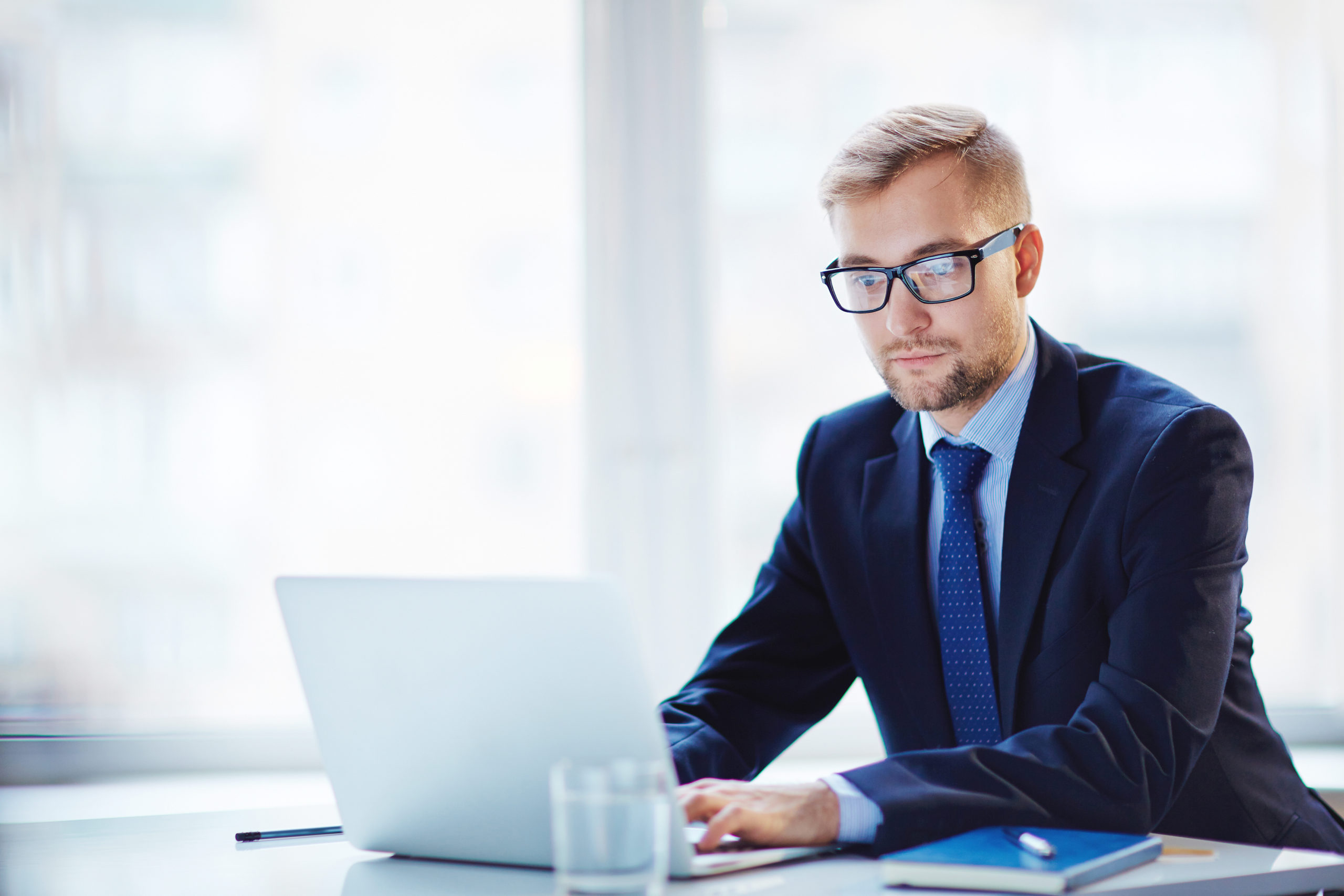 young-businessman-working-laptop-office-395012614