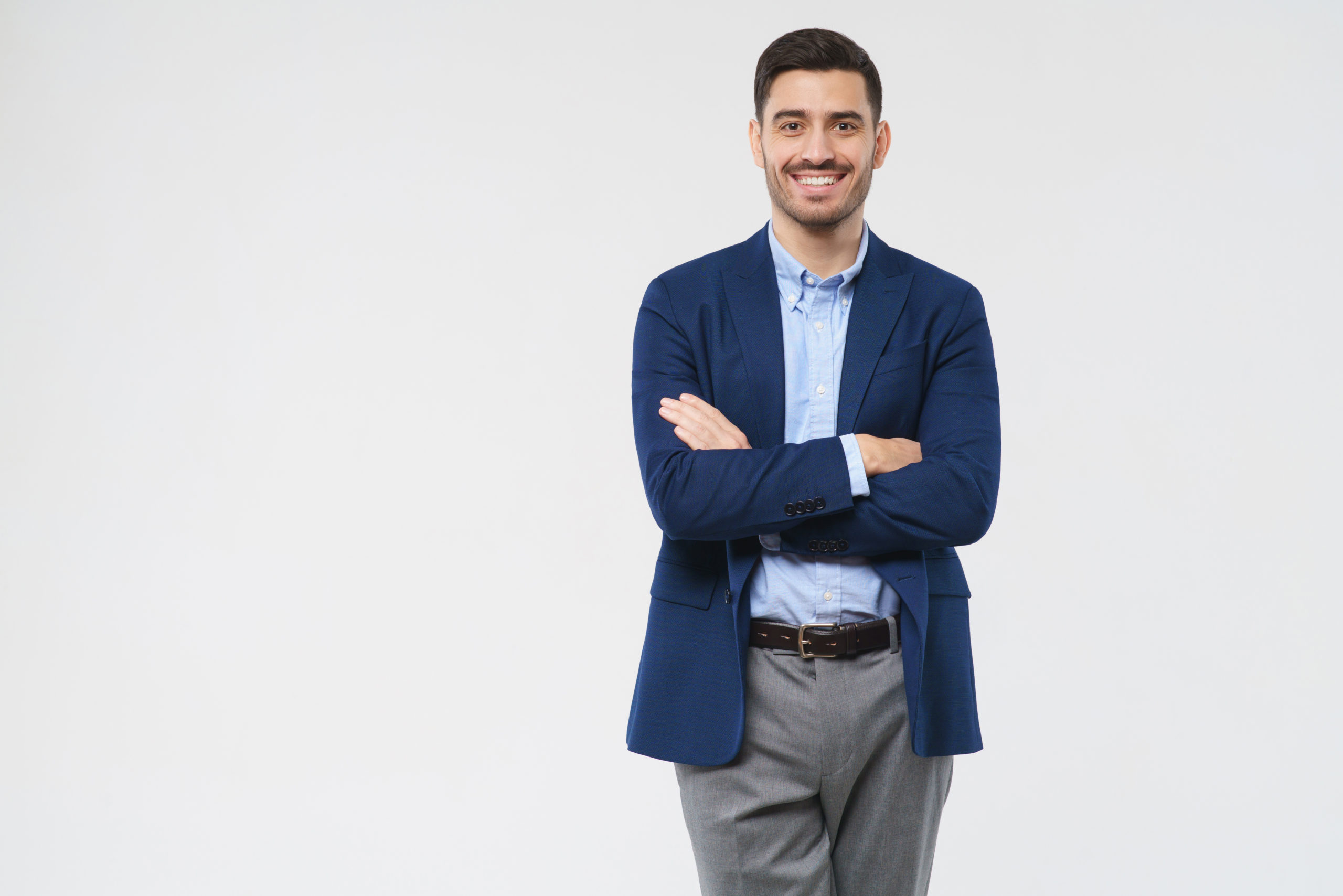 Young,Smiling,Businessman,Standing,With,Arms,Crossed,,Isolated,On,Gray